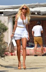 Victoria Silvstedt browses hats worn by a vendor while relaxing at Club 55