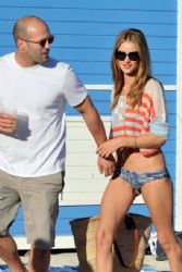 Jason Statham and Rosie Huntington-Whiteley hold hands as they leave the beach in Miami