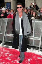 Simon Cowell braves the snow as he walks the red carpet ahead of the